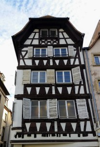 A white half timbered house with open white shutters