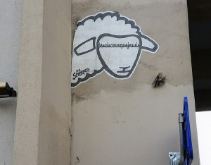 "A sheep's head on a wall that instead of eyes has the phrase ""jesuisceuxquejesuis"" in longhand"