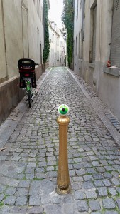 a small cobbled street with a pole in the foreground. The sphere that sits on top of the pole has a big green iris painted on it, so it looks like an eye