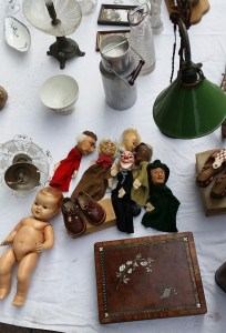 several hand puppets next to another naked doll, a small milk churn and a green table lamp and baby shoes