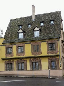 A house with elaborate decorations around the windows and one of the 8 windows is actually painted on.