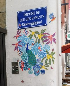 "A street sign saying ""Impasse Jeu des enfants / Kinderspielgässel"" with a colourful peacock and flowers painted below it"