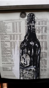 An old menu painted over with an image on a beer bottle