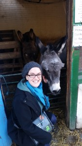 Verena crouching next to a donkey and smiling