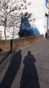 A graffiti of a giant magpie half-covered by a leafless tree