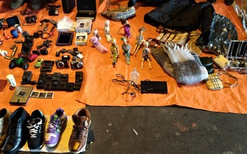 Old Barbie dolls next to handbags, shoes, and used phone batteries