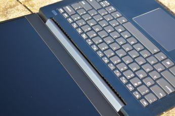 Výdech ventilátoru v žlábku mezi základnou a krytkou pantů obrazovky.