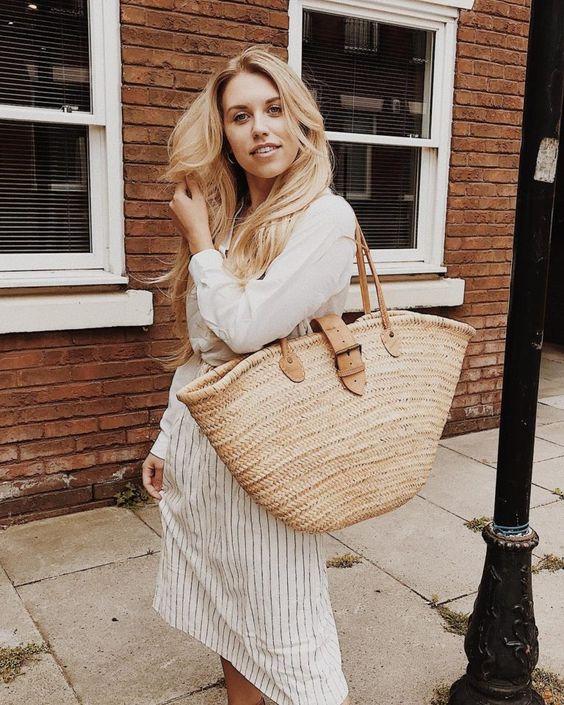 Mulher loira com bolsa de palha grande