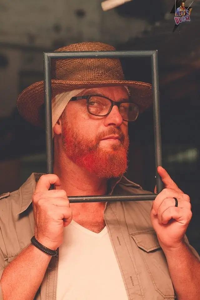 Homem vestido de Van Gogh segurando uma moldura em frente ao rosto