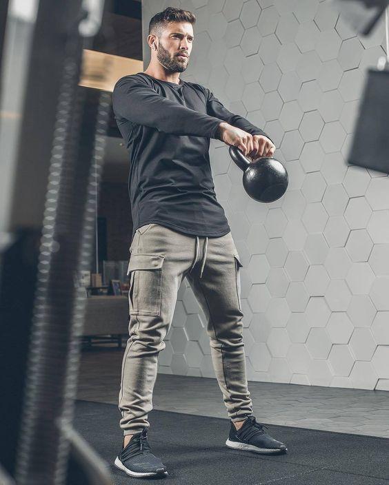 Homem com camiseta manga longa e calça na academia