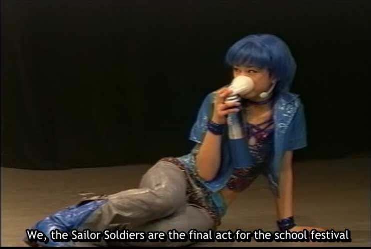 Ami sitting on the stage with a cup to her face during the revision of the Black Lady musical