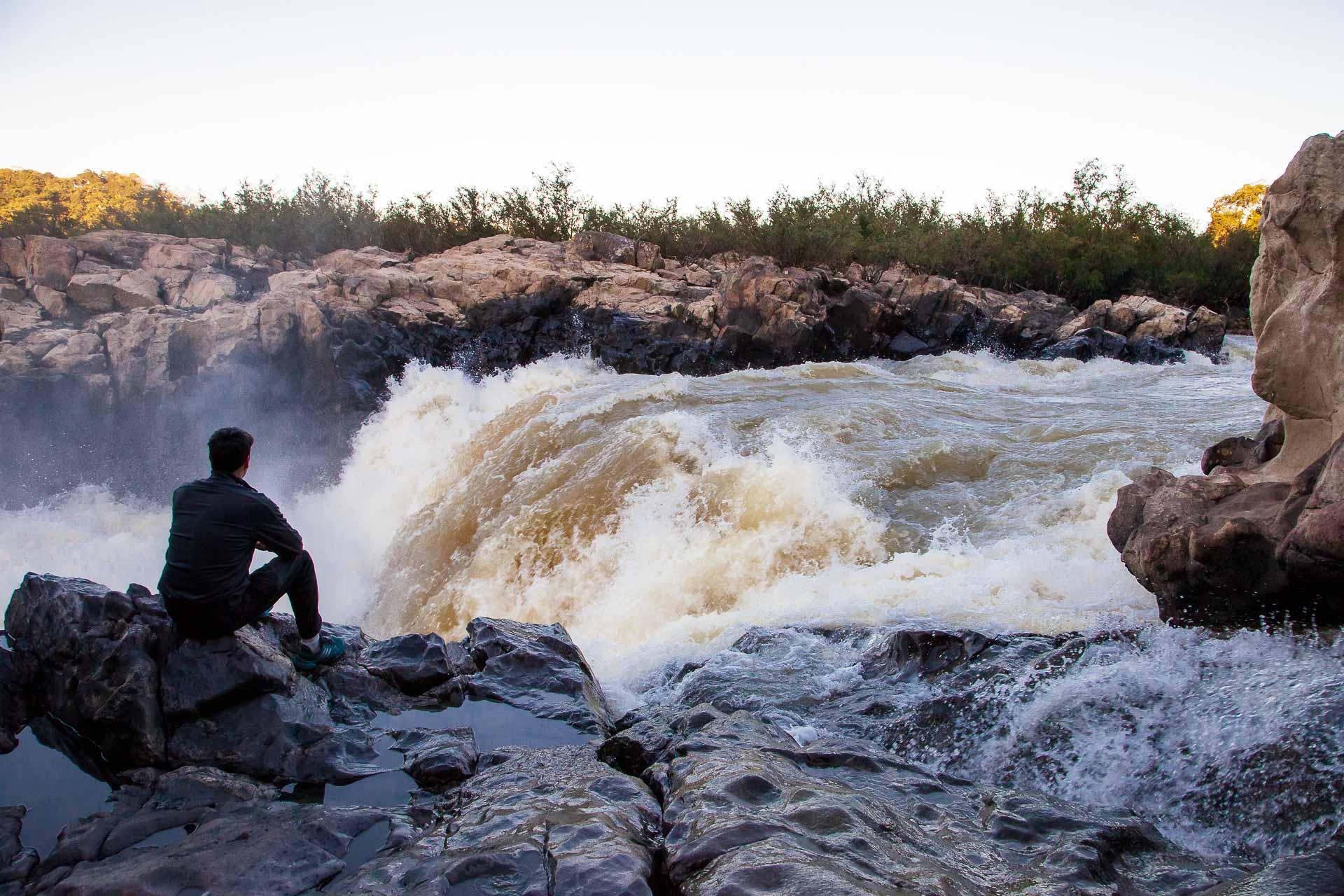 Homem contempla as fortes corredeiras do Rio Itajaí-Açu em Blumenau