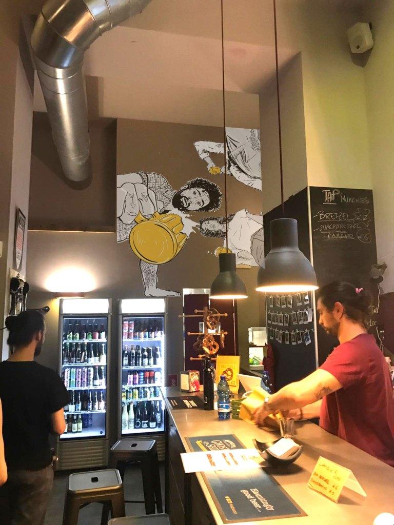 Interno della birreria TAP con un murale sullo sfondo