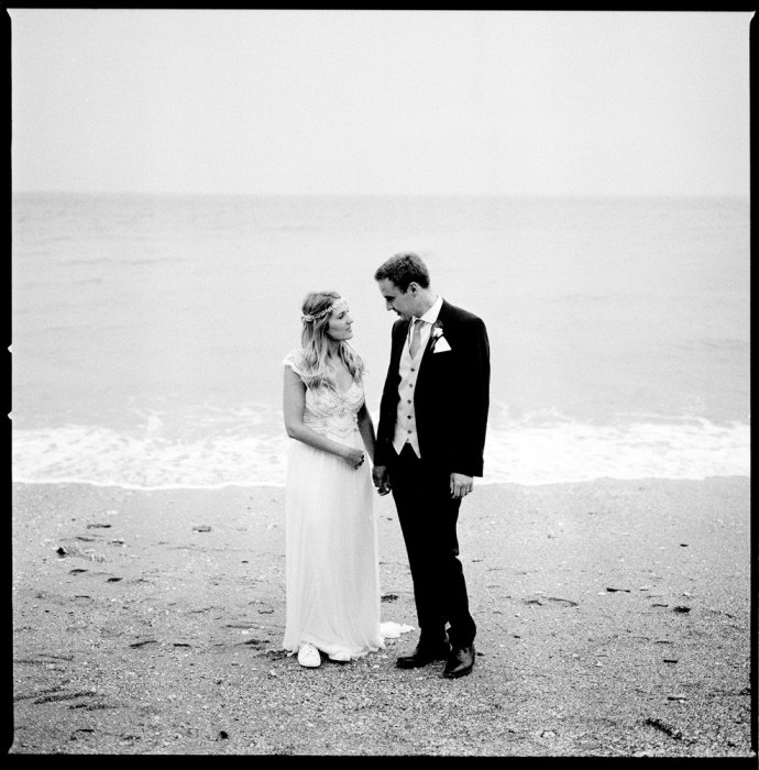 The Bride and Groom made an investment in wedding photography stood on a beach next to the sea