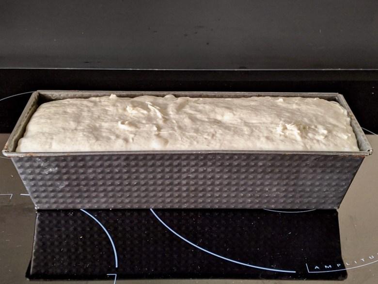pâte à pain levée jusqu'en haut d'un moule à cake