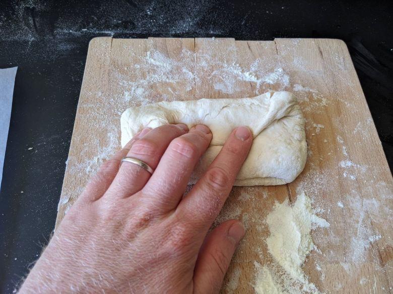 main qui replit d'un tiers un paton de pain