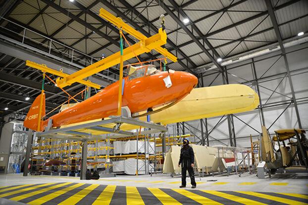 Dans un hangar de Dugny (Seine-Saint-Denis), un planeur aux ailes enlevées est hissé sur une plate-forme pour être placé sur une mezzanine.