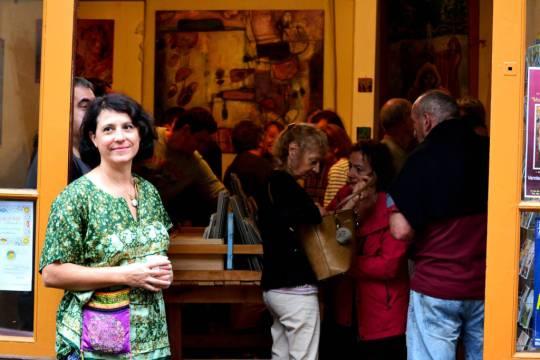 Christine Garuet devant l'Atelier, le jour du vernissage. Comme on le voit, l'exposition a de nombreux visiteurs. Au fond, on peut apercevoir une peinture abstraite, «La machine à écrire».