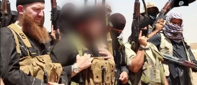 Des membres de l'État islamique, incluant son chef militaire, Abu Omar al-Shishani (à gauche), et le cheikh Abu Mohammed al-Adnani (en flouté).