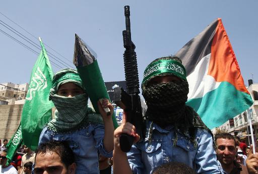 Des enfants palestiniens brandissent des armes en plastique et portent des foulards aux symboles du Hamas lors d'une manifestation à Hébron le 15 août 2014 © Hazem Bader AFP/Archives