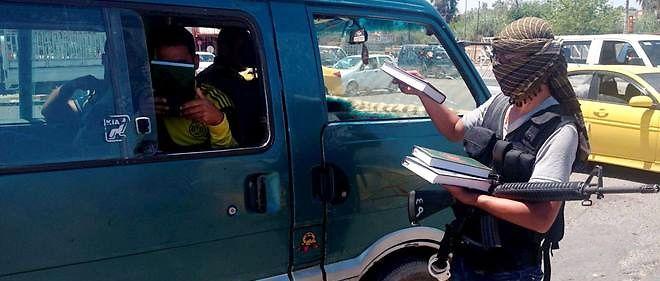 À Mossoul, en 2014. Dans le fief de Daech en Irak, un combattant distribue le Coran. Désormais, mal répondre à des questions sur le livre saint est puni d'amendes.