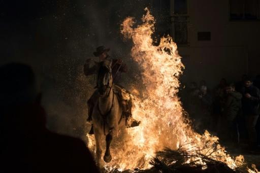 Un cavalier et sa monture sautent par-dessus les flammes pendant la fête des Luminarias à San Bartolomé de Pinares, dans le centre de l'Espagne, le 16 janvier 2018 © GABRIEL BOUYS AFP