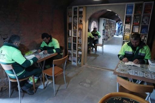 Des hommes lisent des livres dans une bibliothèque créée par des éboueurs d'Ankara, le 9 janvier 2018 © ADEM ALTAN AFP