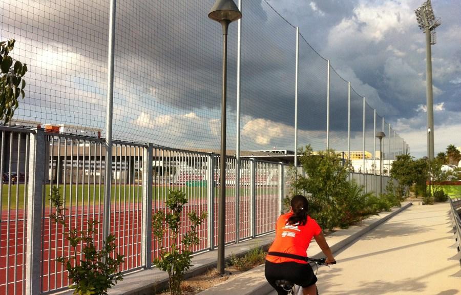 Sur une piste cyclable de terre battue, une cycliste, vue de dos, se déplace le long d'un haut grillage qui nous sépare des pistes de courses rouges autour du grand espace vert du stade. De grands nuages défilent dans le ciel probablement emportés par le vent dans une autre direction. Photo prise le 8 septembre 2015 par Michel Lafaye.