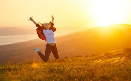 Glückliche Frau springt in den Himmel bei Sonnenaufgang