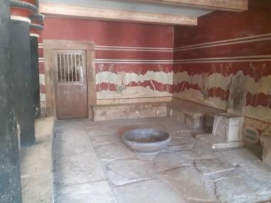 Salle du trône: Evans imaginait le roi légendaire Minos tenant sa cour assis sur le trône d'albâtre de cette salle superbement proportionnée. Toutefois, le bassin lustral et la fresque des griffons laissent penser que la salle était utilisée à des fins religieuses, et sans doute sous l'autorité d'une prêtresse.