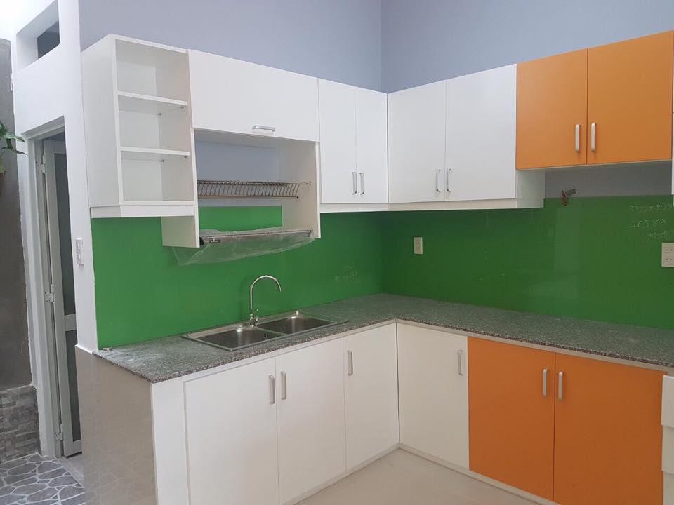 Bếp thiết kế rộng với tủ bếp trên dưới, mặt bếp bằng đá và chậu rữa