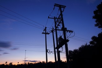 Transformers of an electrical post with power lines at sunset.
