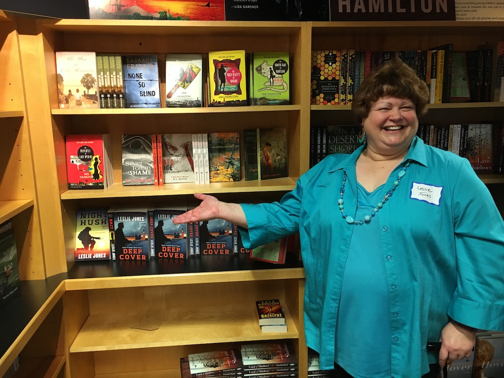 Leslie Jones standing in front of a bookshelf showcasing her books