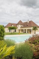 Maison périgourdine vue d'extérieur avec une piscine parfaitement intégrée au paysage de Dordogne