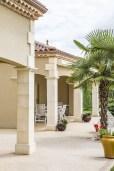 Maison périgourdine vue d'extérieur montrant l'aménagement de la terrasse avec ses imposants piliers extérieurs en marbre