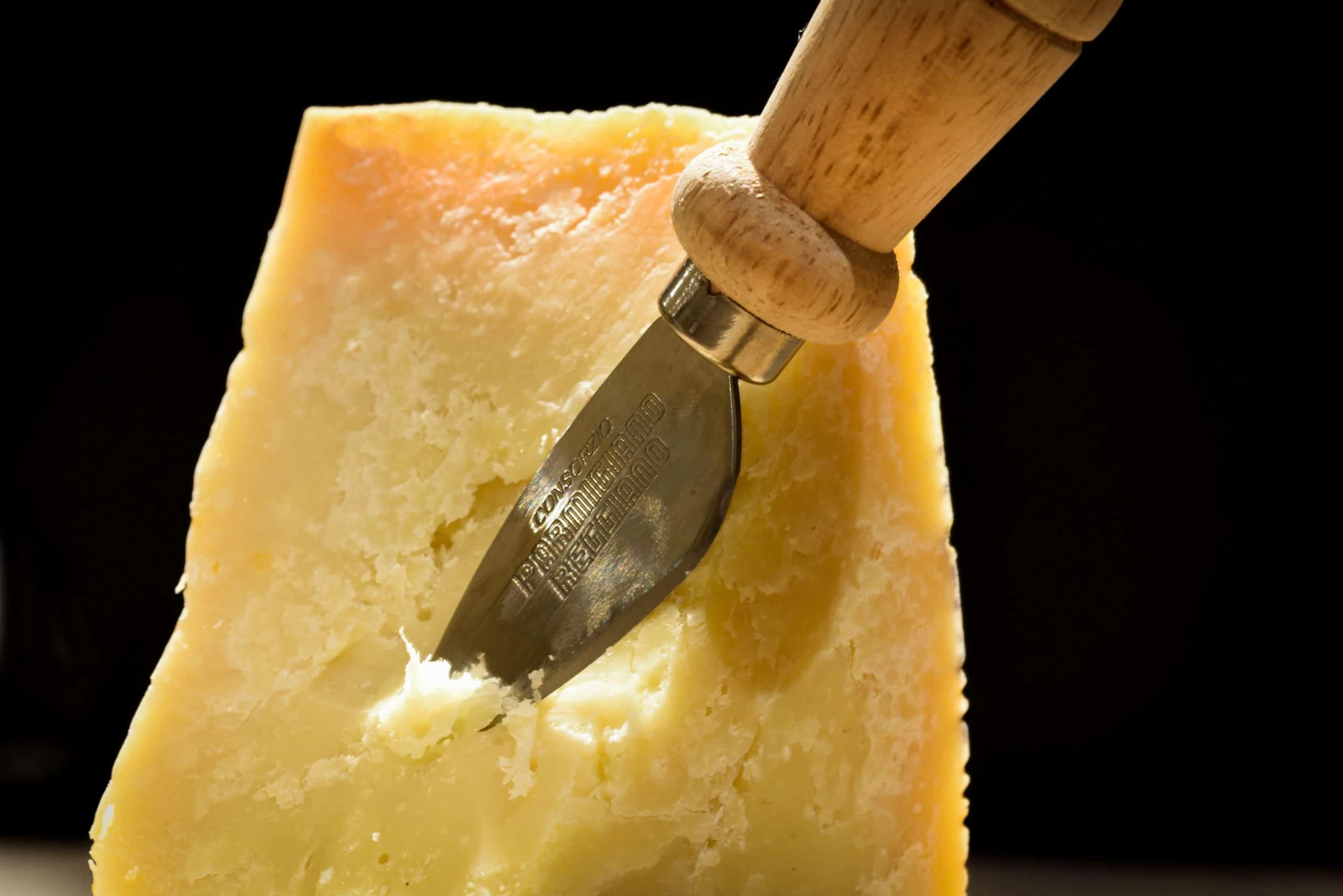 bloc de parmesan entrain d'être découpé