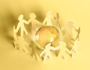 Paper people standing in a circle around glass