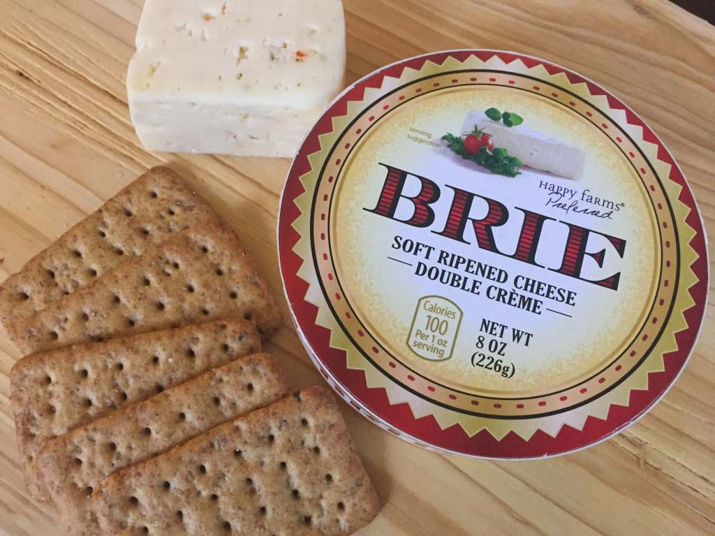 brie, crackers and havarti on cheese board tray