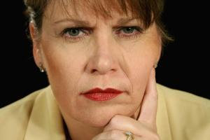 An image of a woman scowling, an example of a bad expression to make in a LinkedIn headshot.