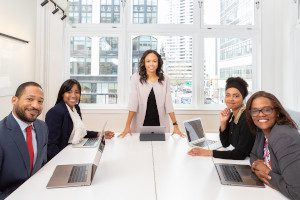 A stock photo of a smiling woman standing at the head of a table with other seated professionals. Photo by Rebrand Cities from Pexels.