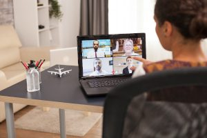 A stock photo displaying a woman on a video call on a laptop, illustrating the importance of setting up a shot beforehand for a video interview.