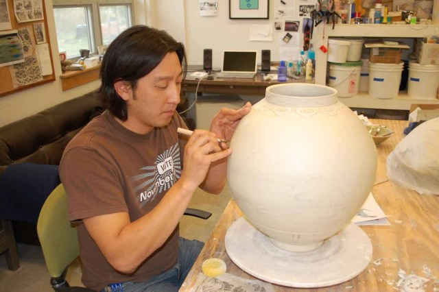 Director Steve Young Lee decorating a vase in the studio