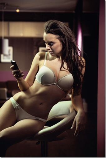Sexy young lady writing a sext message