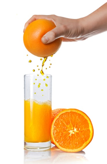 Squeezing orange juice pouring into glass isolated on white