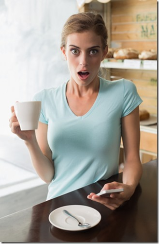 Shocked woman with coffee cup reading text message coffee shop