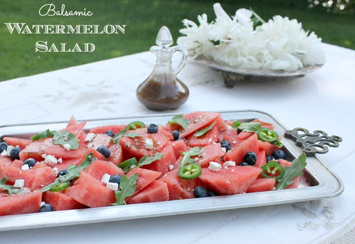 A large platter of balsamic watermelon salad, next to a jug wil salad dressing on it