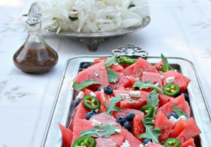 A watermelon salad on a platter, next to a balsamic dressing