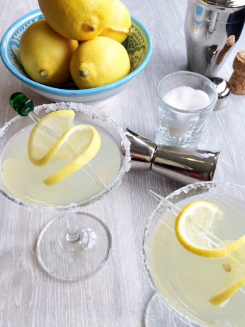 A set up for making lemon cocktails. A bowl of lemons, shot class of sugar, 2 martini glasses full of cocktail with a lemon twist on a skewer.