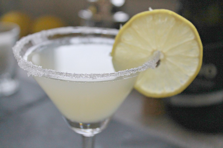 A martini glass with a fizzy lemon cocktail in it. The rim of the glass has sugar on it and there is a slice of lemon