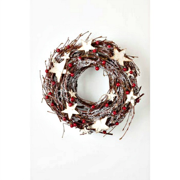 A Christmas wreath made up of twigs in a circular shape. It is dotted with red berries, fake frost and large cream coloured stars